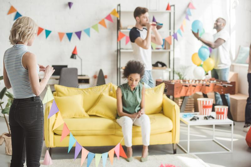 Multiethnic young women holding string with party garlands while their friends standing behind. With decor stock photos