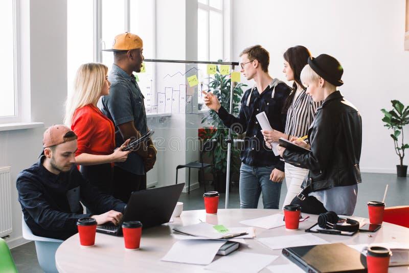 Multiethnical ludzie biznesu spotyka przy biurem w przypadkowych ubraniach i używają pocztę ono zauważa dzielić pomysł brainstorm obrazy royalty free