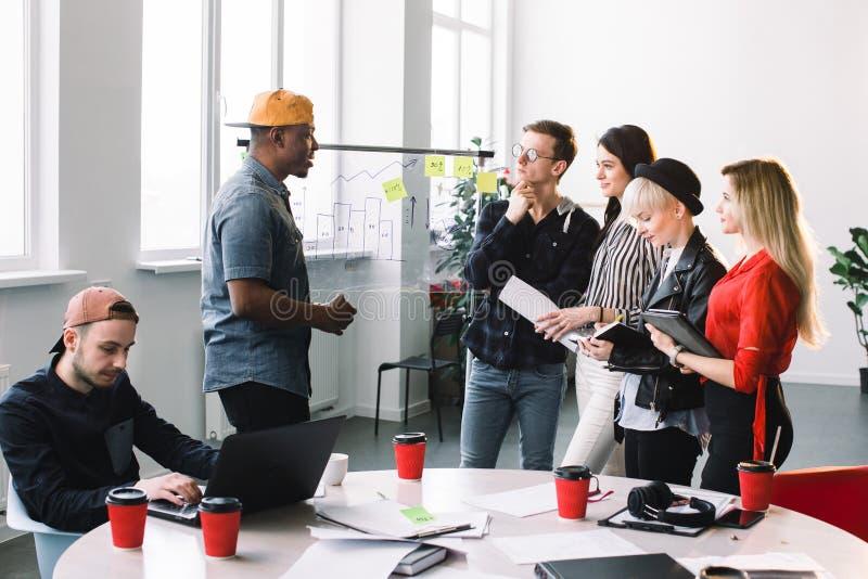 Multiethnical ludzie biznesu spotyka przy biurem w przypadkowych ubraniach i używają pocztę ono zauważa dzielić pomysł brainstorm zdjęcie royalty free