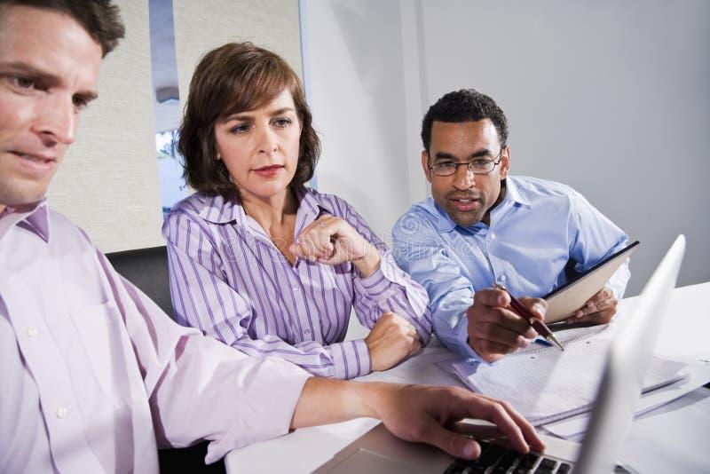 Multiethnische Büroangestellte, die an Projekt arbeiten lizenzfreie stockfotografie