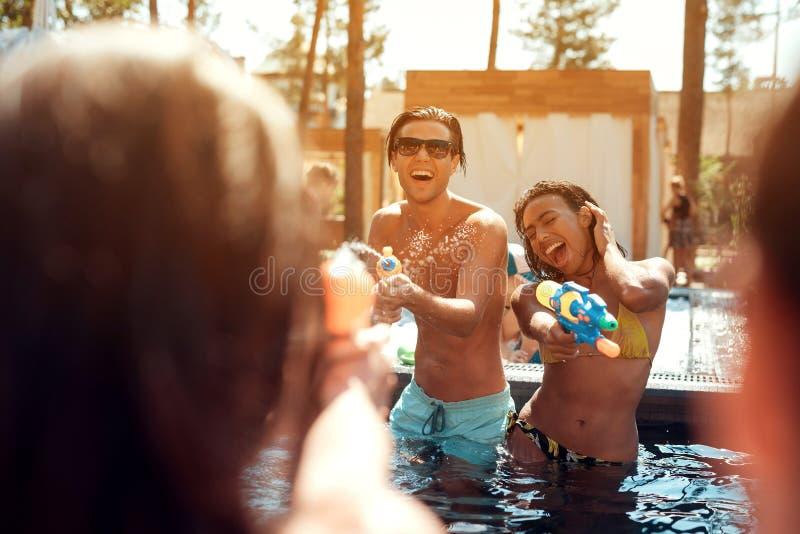 Multiethnische Firma von Freunden im Swimmingpool an der Sommerzeit Schwimmenpool-party lizenzfreies stockbild