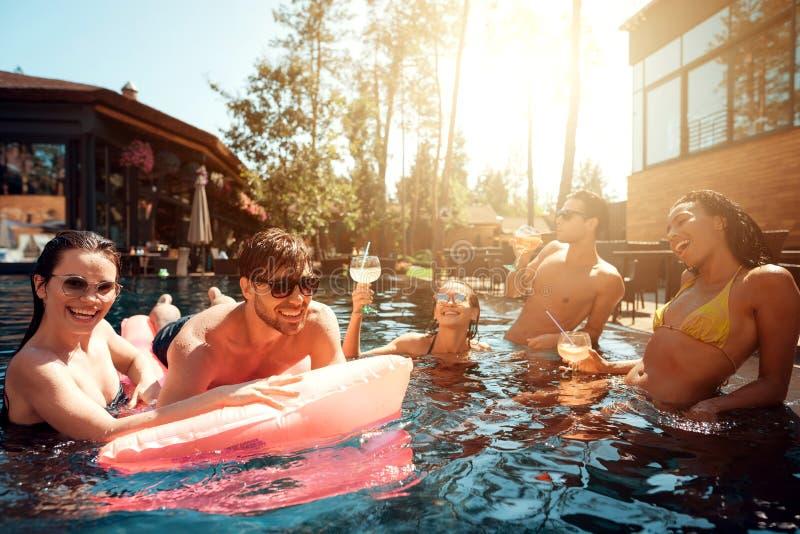 Multiethnische Firma von Freunden im Swimmingpool Firma von jungen Leuten verbringen Wochenende im Pool stockbild