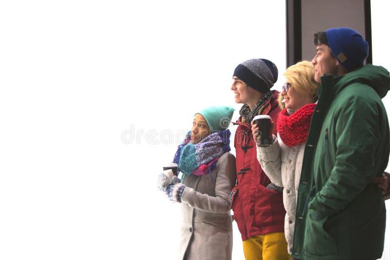 Multiethnische Freunde, die weg gegen klaren Himmel während des Winters schauen lizenzfreie stockfotografie