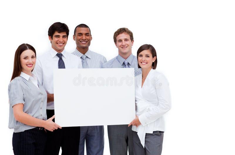 Multiethnische Geschäftsleute, die eine weiße Karte anhalten lizenzfreies stockfoto