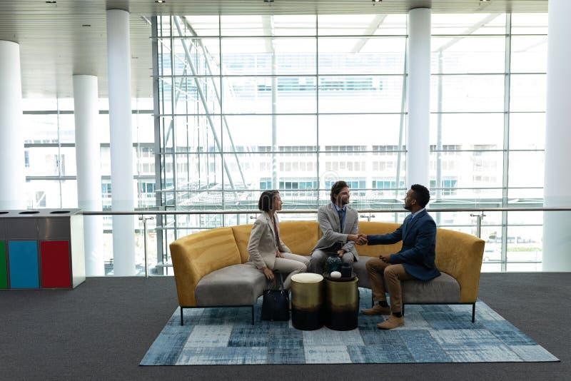 Multiethnische Geschäftsleute, die mit einander in der Lobby sitzen und sich besprechen lizenzfreies stockbild