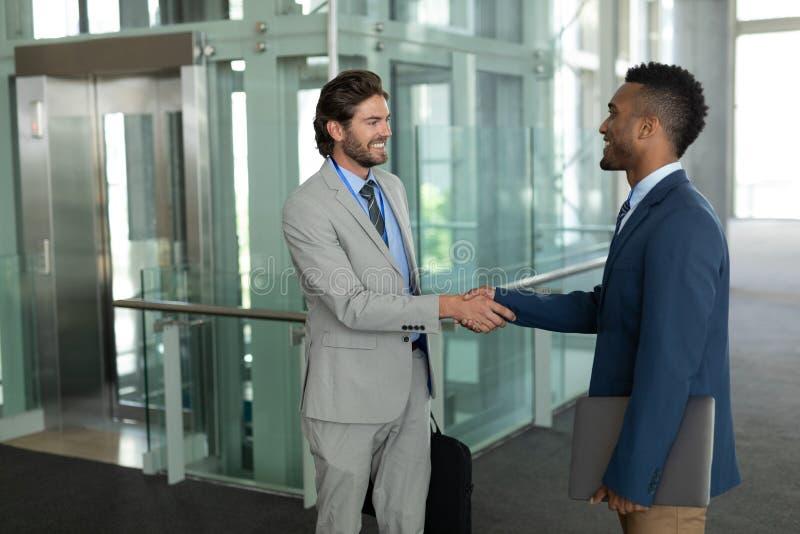 Multiethnische Geschäftsmänner, die Hände mit einander im Korridor rütteln lizenzfreie stockbilder