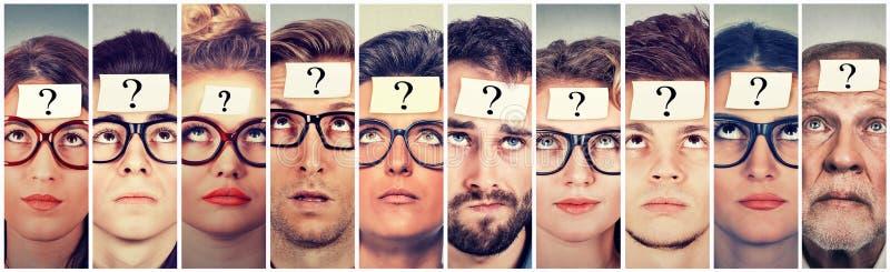 Multiethnische Gruppe denkende Leute mit Fragezeichen lizenzfreie stockfotos