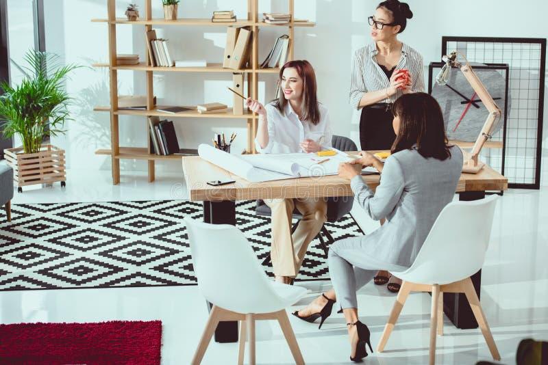 Multiethnische Gruppe junge Geschäftsfrauen, die mit Plänen und der Diskussion arbeiten lizenzfreies stockfoto