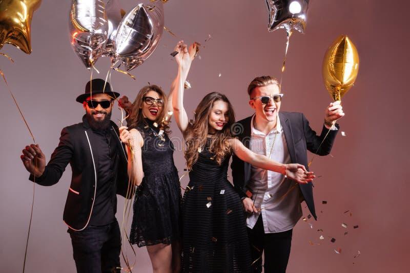 Multiethnische Gruppe junge lächelnde Leute, die Partei tanzen und haben stockbild