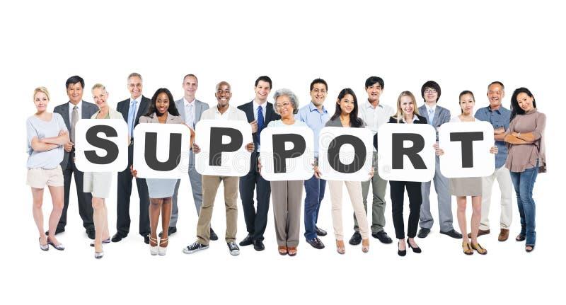 Multiethnische Gruppe von Personen, die Buchstabe-Unterstützung hält stockfotografie