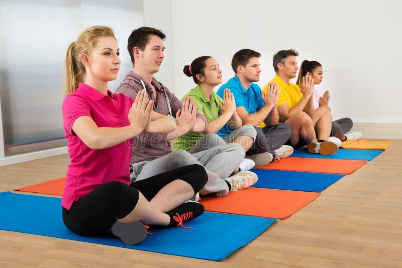 Multiethnische Gruppe von Personen, die Meditation tut stockbilder