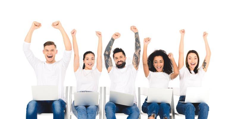 multiethnische Gruppe von Personen unter Verwendung der Laptops und Freuen mit den Händen über dem Kopf lokalisiert lizenzfreies stockbild