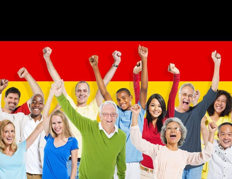 Multiethnische Leute bewaffnen gehißte und deutsche Flagge lizenzfreie stockfotos
