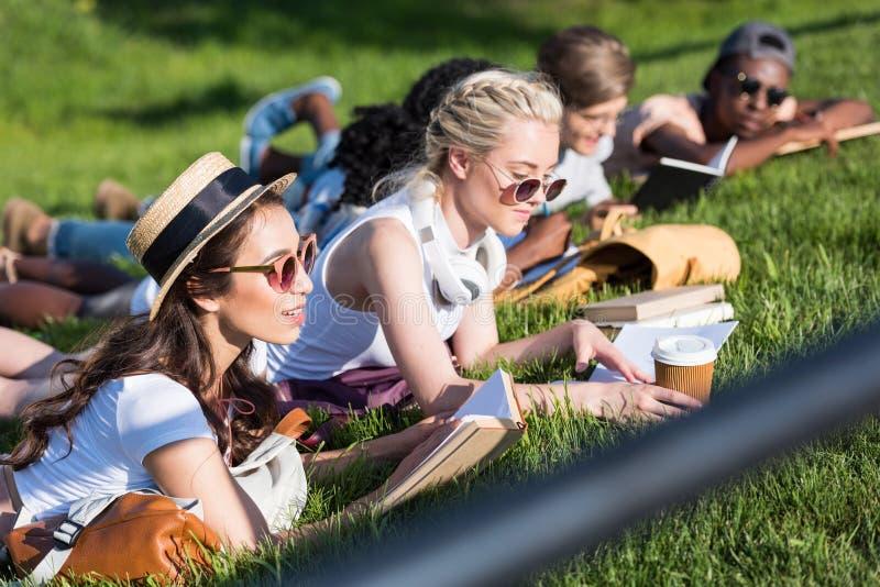 Multiethnische Mädchenlesebücher beim Lügen auf Gras und Studieren im Park lizenzfreies stockfoto