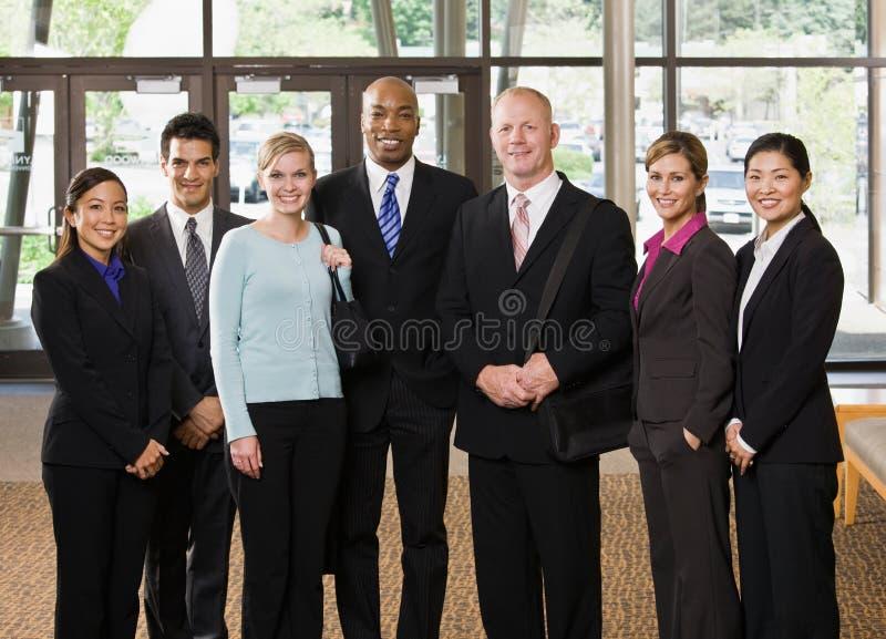 Multiethnische Mitarbeiter, die in der Vorhalle aufwerfen lizenzfreies stockfoto