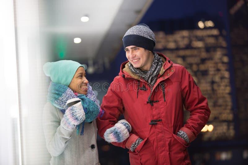 Multiethnische Paare, die an der Dämmerung während des Winters sich unterhalten stockbilder