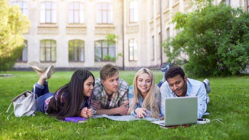 Multiethnische Studenten, die auf Gras und aufpassendem lustigem Video auf Laptop, Freunde liegen stockfoto