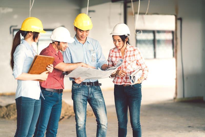 Multiethnische verschiedene Gruppe Ingenieure oder Teilhaber an der Baustelle, zusammen arbeitend an Gebäude ` s Plan stockfoto