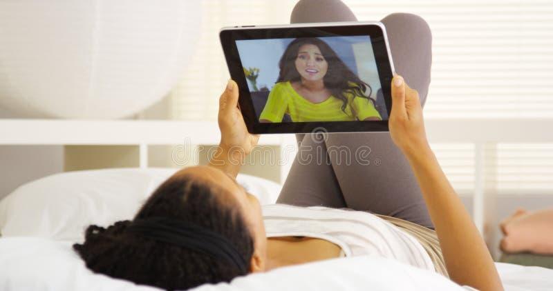 Multiethnisches Freunde vidoe, das zu Hause mit Tablette auf Bett plaudert stockfotografie