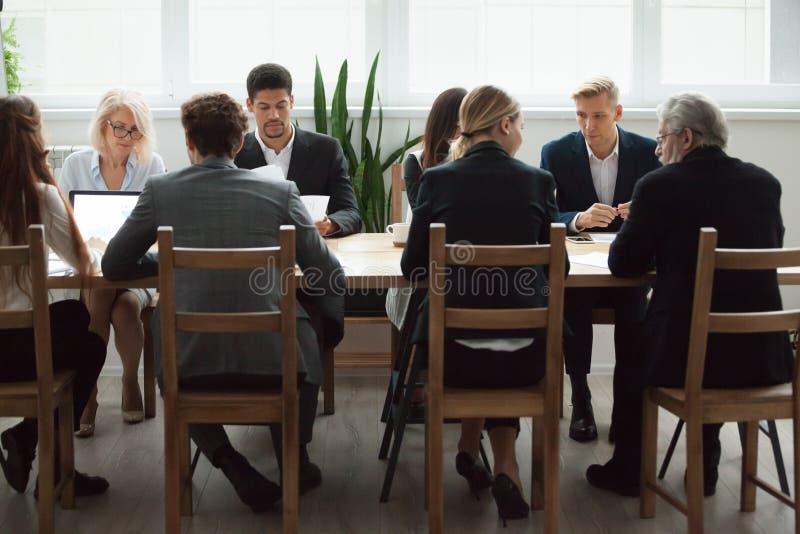 Multiethnisches Geschäftsteam, das am Konferenztische, negotiat sitzt lizenzfreie stockfotos