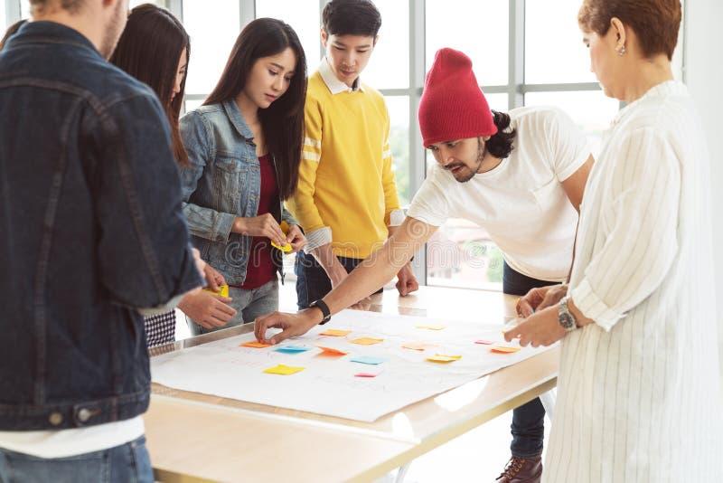 Multiethnisches kreatives Team, das zusammenarbeitet, auf Tabelle an Arbeitsplatz sich trifft und gedanklich löst Startverschiede stockfoto