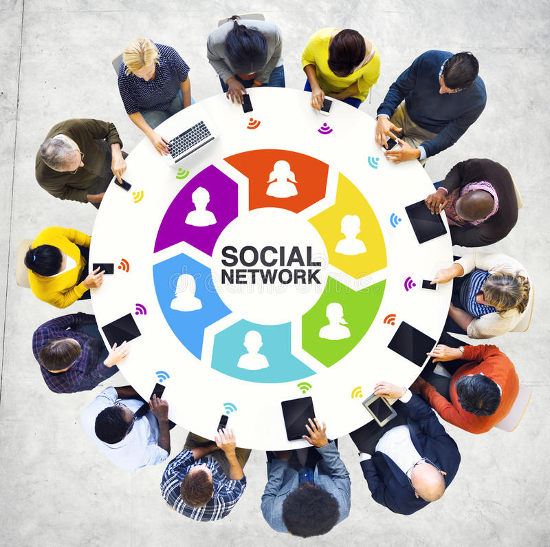 Multiethnisches Leute-Social Networking mit Digital-Geräten stockbilder