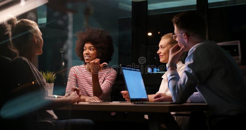 Multiethnisches Startgeschäftsteam im Nachtbüro stockbild