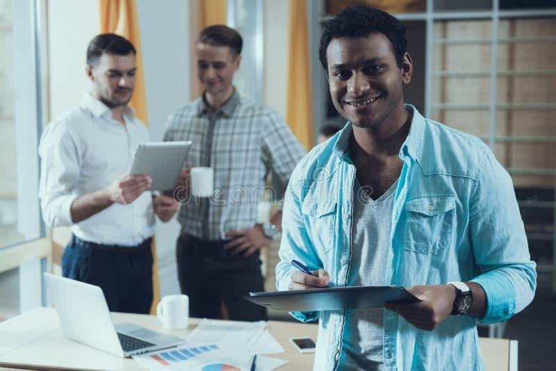 Multiethnisches Team von jungen erfolgreichen kreativen Leuten arbeitet an allgemeinem Projekt start lizenzfreie stockbilder