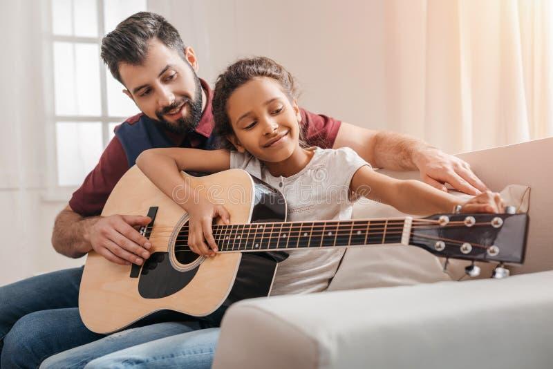 Multietnisk fader och dotter som hemma spelar gitarren på soffan arkivbild
