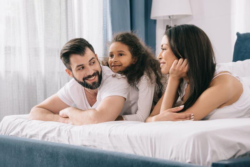 Multietnisk familj med ett barn som tillsammans ligger i säng arkivfoton