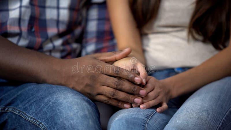 Multietnisk familj som rymmer händer, förhållande av förälskelse, mjukhet och förtroende arkivfoto