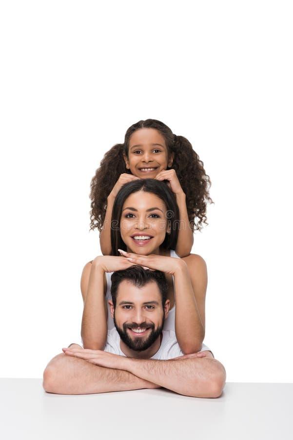 Multietnisk familjbenägenhet på den vita tabellen och le på kameran royaltyfria foton