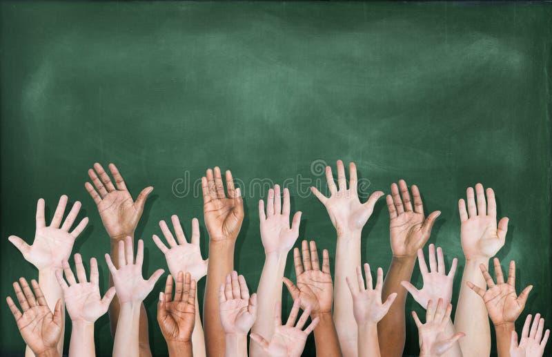 Multietnisk grupp av händer som lyfts med svart tavla royaltyfri bild