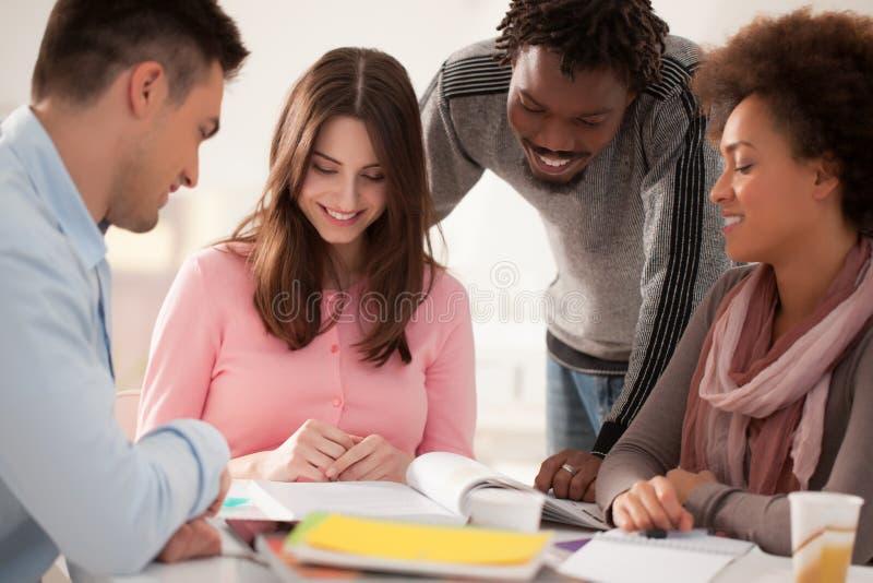 Multietnisk grupp av högskolestudenter som tillsammans studerar royaltyfria foton