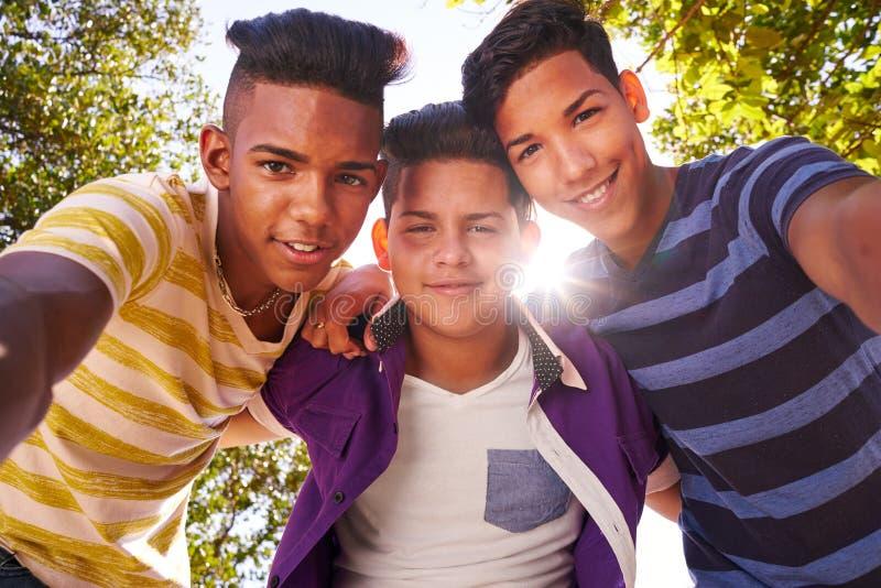 Multietnisk grupp av tonåringar som omfamnar som ler på kameran royaltyfria bilder