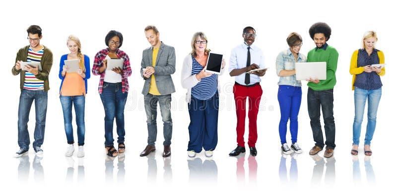 Multietnisk grupp människor som använder Digital apparater arkivbild