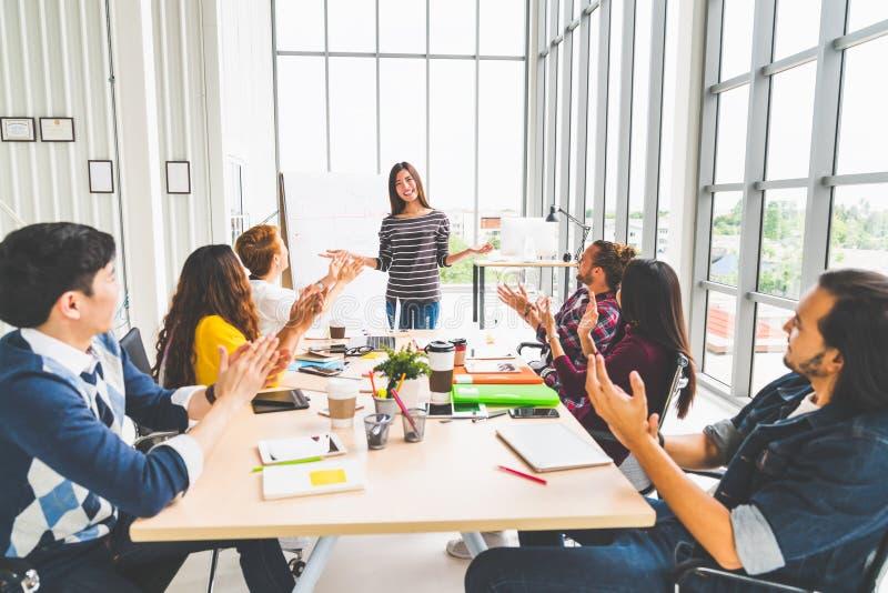 Multietnisk olik grupp av idérika lag- eller affärscoworkerapplådhänder i projektpresentationsmöte som leder vid den asiatiska kv royaltyfri foto