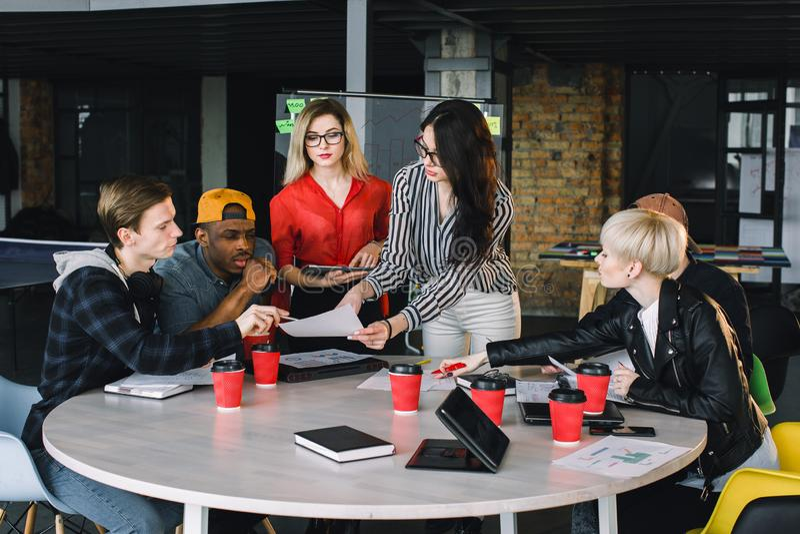 Multietnisk olik grupp av idérikt lag, tillfälligt affärsfolk eller högskolestudenter i strategiskt möte eller projekt royaltyfria bilder