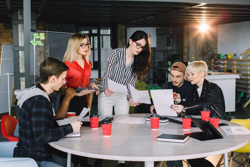 Multietnisk olik grupp av idérikt lag, tillfälligt affärsfolk eller högskolestudenter i strategiskt möte eller projekt royaltyfria foton