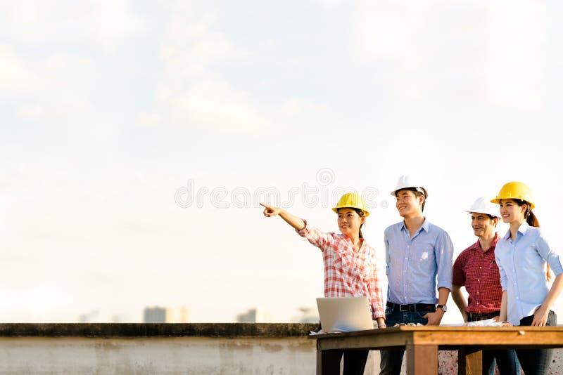 Multietnisk olik grupp av teknikerer eller affärspartners på konstruktionsplatsen som pekar in mot kopieringsutrymme på himmel un royaltyfria bilder