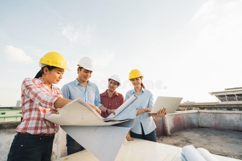 Multietnisk olik grupp av teknikerer eller affärspartners på konstruktionsplatsen som tillsammans arbetar på building& x27; s-rit arkivfoton