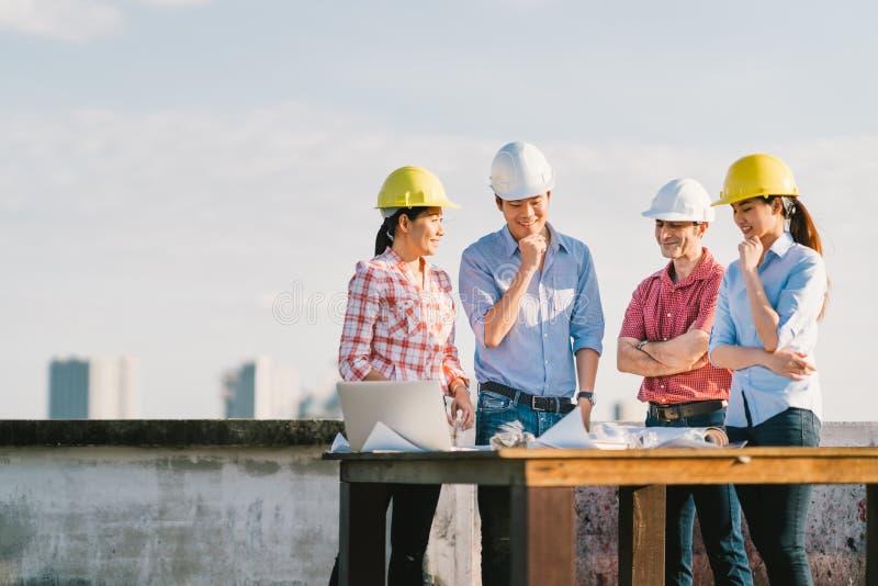 Multietnisk olik grupp av teknikerer eller affärspartners på konstruktionsplatsen som tillsammans arbetar på ritning för byggnads royaltyfri fotografi