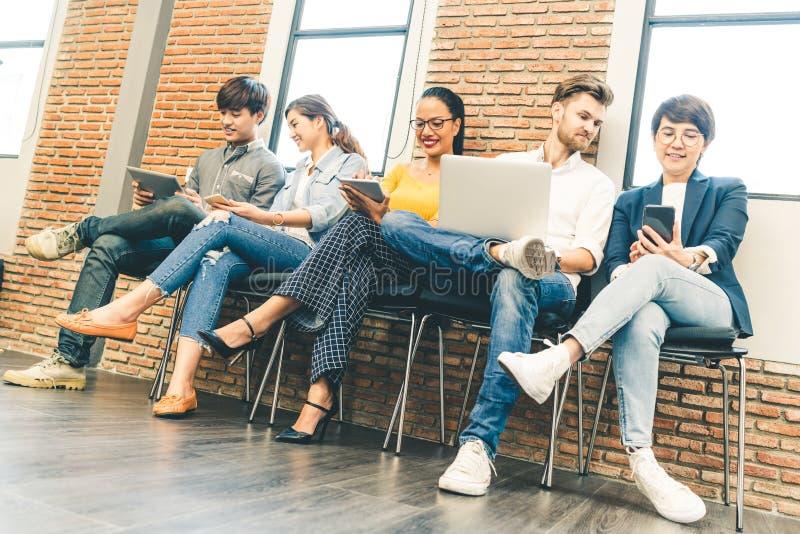 Multietnisk olik grupp av ungt och vuxet folk som tillsammans använder smartphonen, bärbar datordator, digital minnestavla arkivbild