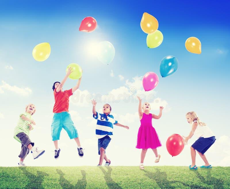 Multietniska barn som spelar utomhus ballonger fotografering för bildbyråer