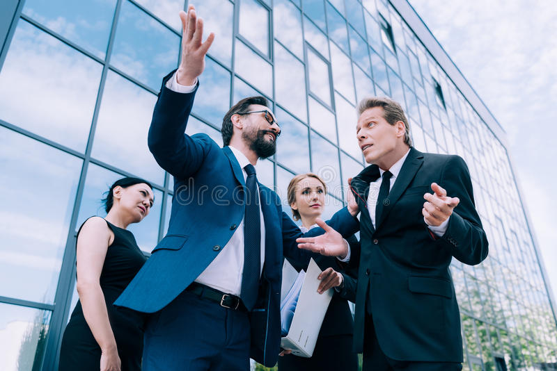 Multietniska businesspeople som har diskussion nära modern kontorsbyggnad royaltyfri foto