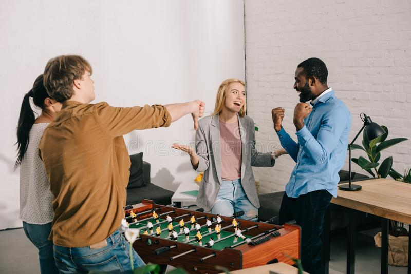 multietniska businesspeople som spelar tabellfotboll och gör olika gester i modernt arkivbilder