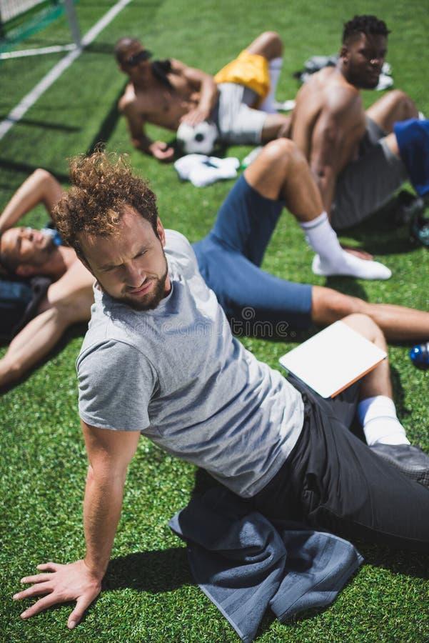 Multietniska fotbollspelare som vilar på fotbollfält efter lek arkivfoto
