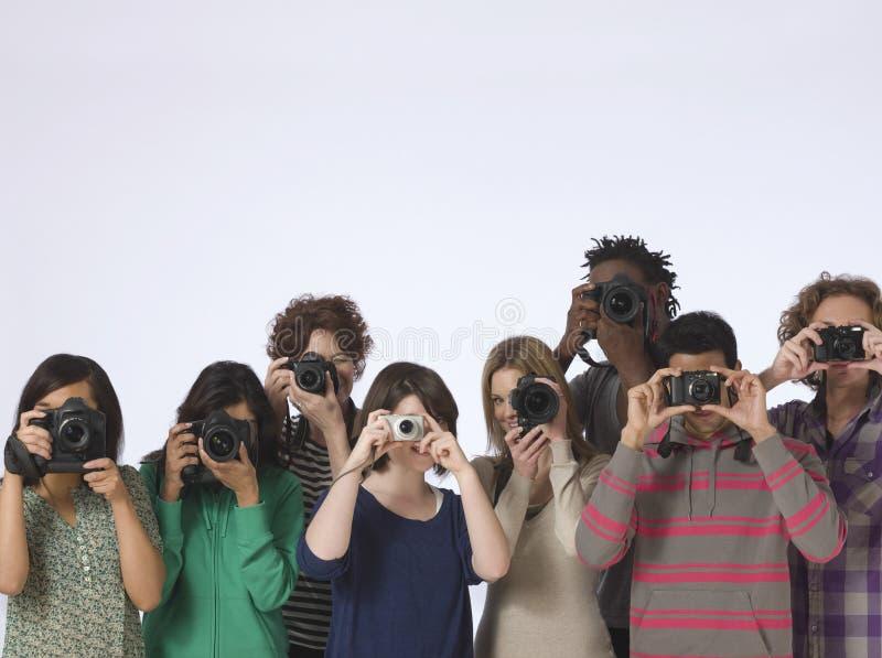 Multietniska fotografer som tar foto royaltyfri foto