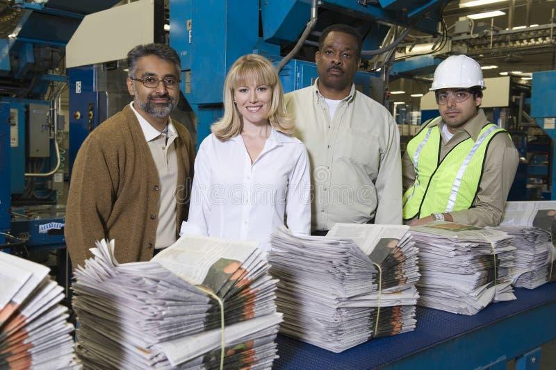 Multietniska operatörer med bunten av tidningar i fabrik royaltyfri fotografi