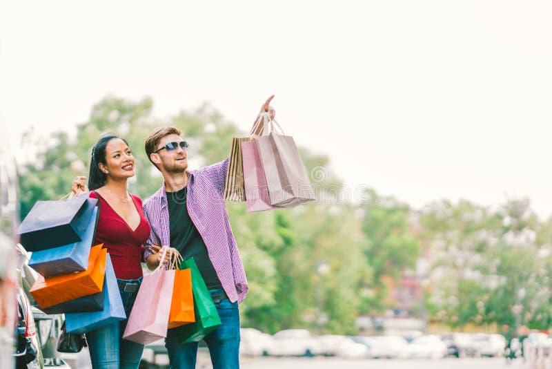 Multietniska par med shoppingpåsar, man som pekar på kopieringsutrymme på himmel Förälskelse, tillfällig livsstil eller shopaholi arkivbild